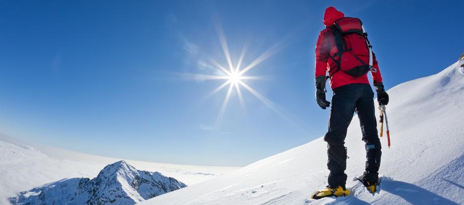 Mountaineer reaches the top of mountain.